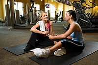 Adult Caucasian female with personal trainer at gym.