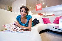 Young woman with brochure on sofa in shop, smiling, portrait (thumbnail)