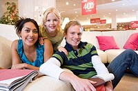 Family of three on sofa in shop, smiling, portrait