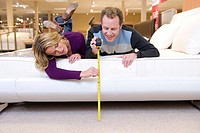 Young couple measuring bed in furniture shop