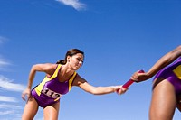 Female relay athletes passing baton blurred motion