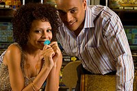 Young couple gambling, woman with gambling chip, smiling, portrait