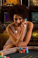 Young woman gambling, holding gambling chip, smiling, portrait