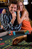 Young couple gambling, man with gambling chip, smiling, portrait