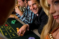 Man gambling at roulette table, smiling, portrait