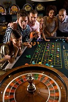 Men and women gambling at roulette table in casino, elevated view