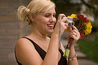 A bridesmaid takes a photo while holding a bouquet of gerbera daisies.