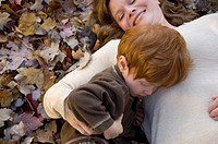 A 3_year_old boy plays with his mother in fall leaves.