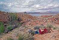 Hiker looks at Henry Mountains from desert beside Lake Powell, Utah.