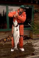 Fisherman holding a 40_lb salmon caught in British Columbia.
