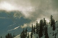 Clouds drift past snow_covered slopes under Mount Shuksan.