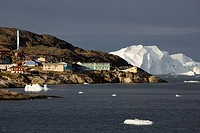 View of a fishing community and a distant iceberg.