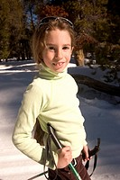 A young girl standing in the snow.