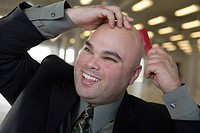 View of a businessman combing baldhead.