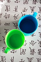 Plastic glasses on tablecloth decorated with oriental designs