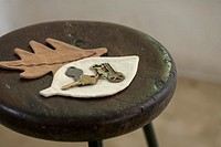 Keys on leaf shaped pad on wooden stool, close_up