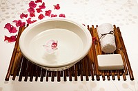White bowl with single orchid, soap and towel