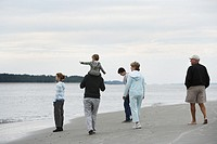 Family including baby boy 15_18 months and teenagers 10_15 walking along beach