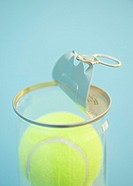 Canister of tennis balls with open lid, close_up