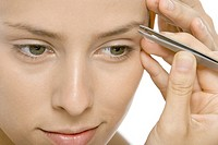 Woman using tweezers to pluck eyebrows, close-up