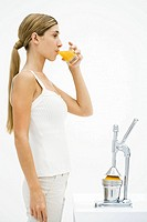 Young woman standing in front of citrus press, drinking freshly squeezed orange juice
