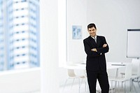 Businessman standing in meeting room with arms crossed, smiling at camera