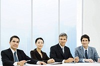 Business associates sitting at meeting table, smiling at camera