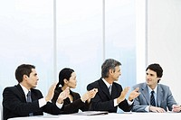 Executives applauding male colleague during meeting