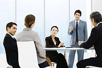 Business associates having meeting, one standing, pointing