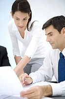 Businessman and female assistant looking at document together