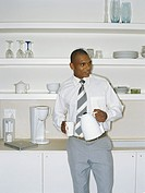 Businessman standing in kitchen holding coffee cup and flask, looking away