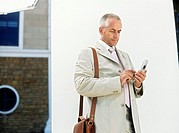 Business man text messaging,standing by white wall