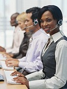 Young woman in row of businesspeople wearing headsets, side view