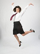 Portrait of young business woman jumping, studio shot