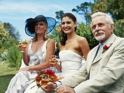 Bride sitting with mature man and mature woman, smiling