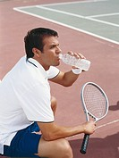 Tennis player holding tennis racquet drinking water, side view