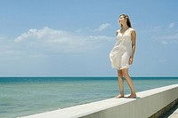 Young woman in sundress standing on low wall beside sea, eyes closed