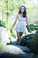 Young woman in slip walking outdoors, arms out, looking at camera