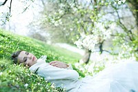 Teenage girl lying in grass, holding flowers, eyes closed