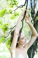 Young woman with arms raised, holding tree branch, eyes closed