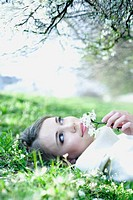 Teenage girl lying on the ground, holding flowers up to face, looking away