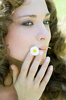 Young woman holding flower in mouth, looking away, close-up