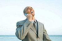 Businessman at the beach using cell phone, laughing, eyes closed