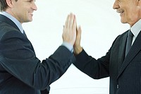 Two businessmen giving each other a high-five, cropped side view