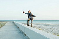 Businessman standing on low wall at the beach, arms out, holding football