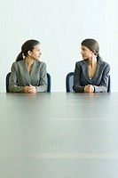 Teenage twin sisters dressed in suits, sitting at table, looking at each other (thumbnail)