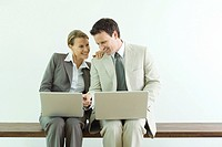 Male and female business associates, both using laptop computers, man pointing to woman's screen