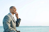 Businessman by the sea using cell phone, smiling, side view