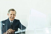 Businessman using laptop computer, smiling at camera, low angle view