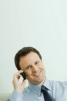 Businessman using cell phone, head tilted, smiling at camera